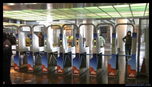 picture of CTA turnstiles with ads for Arizona